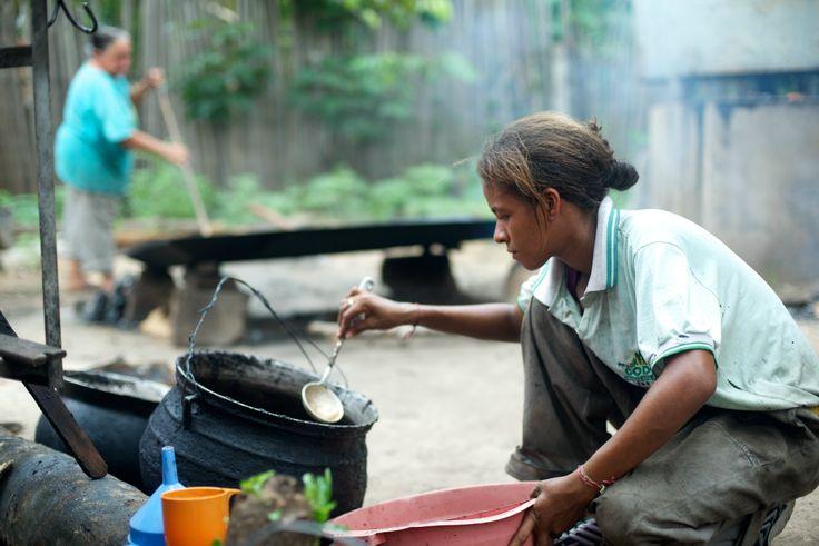 Una mujer extrayendo aceite de semillas de Brasil.