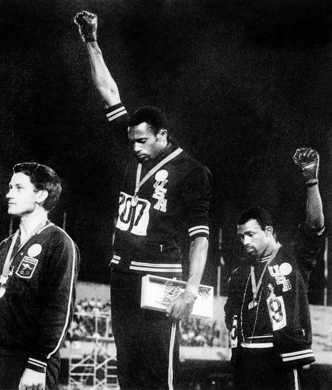 US athletes Tommie Smith (C) and John Carlos (R) raise their gloved fists in the Black Power salute to express their opposition to racism in the USA during the US national anthem, after receiving their medals in 1968 for first and third place in the men's 200m event at the Mexico Olympic Games.