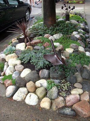 Beautiful curb strip with rocks, succulents and iron artwork. Love this!