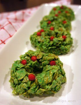 1 stick butter  30 marshmallows (large)  1 teaspoon vanilla  2 teaspoons green food coloring  4 cups cornflakes  Red hot candies