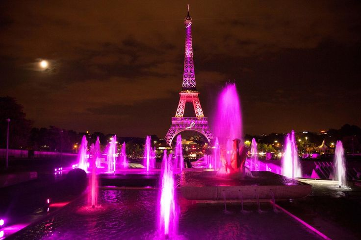 The Eiffel Tower Is Lit Up By Pink And Purple Lights For