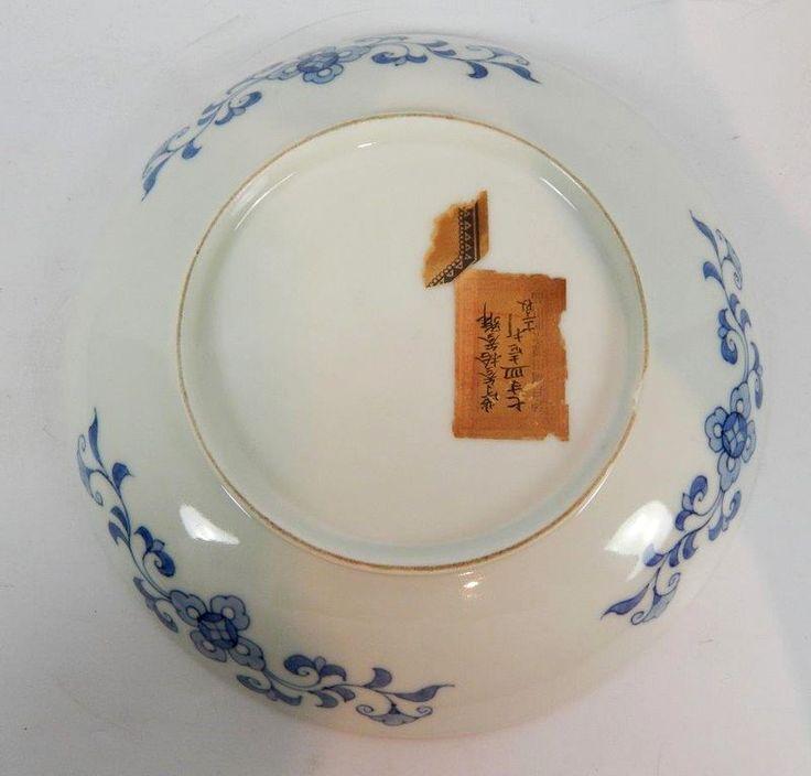 JAPON. Coupe en porcelaine de style Nabeshima à décor moulé en relief d'une carpe blanche dans la brume et d'une autre carpe bleue, au dos branches de fleurs. XIXe siècle. D : 21,9 cm (éclat au talon)