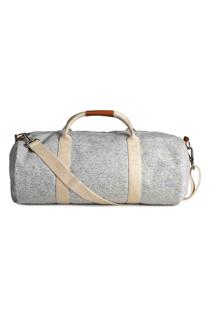 Jersey weekend bag: Cylindrical weekend bag in marled jersey with canvas on the inside, two handles and a zip at the top, an adjustable, detachable shoulder strap and imitation leather details. Diameter 25 cm, length 55 cm.