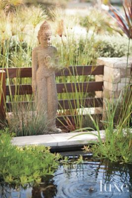 A statue overlooks a modern resort-style home's koi pond.