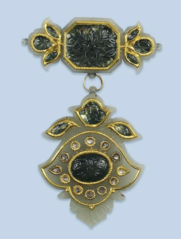 AN INDIAN GEM SET AND DIAMOND JADE PENDANT   The carved celadon-coloured jade pendant inset with carved and foiled glass cabochons, further enhanced with rose-cut diamonds set in gold mounts