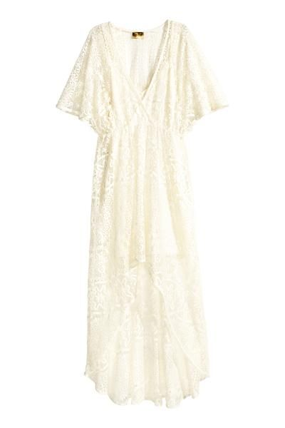 Een jurk van opengewerkt kant met een overslag vooraan, een V-hals, korte vlindermouwen en een naad met smal elastiek in de taille. De rok heeft een asymmet