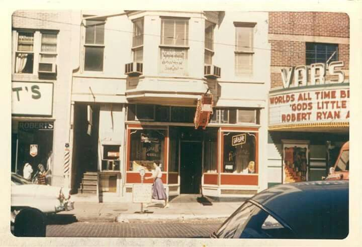 """George Couladis' Esquire Grill (later Mr. Bojangles) on Court St. in Athens, Ohio. Upstairs is the Campus Barber Shop. """"God's Little Acre"""" (1958) is advertised on the Varsity Marquee at the right, starring Robert Ryan, Tina Louise, Aldo Ray, and Buddy Hackett."""