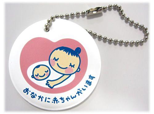 """In Giappone, quando una donna rimane incinta, le viene dato gratuitamente questo oggettino da attaccare alla propria borsa in modo che, anche se è ancora nel primo periodo della gravidanza e la pancia ancora non si nota, le persone intorno se ne accorgano e possano lasciarle il posto. La scritta all'interno significa:「おなかに赤ちゃんがいます」""""Nella pancia ho un bebè""""."""