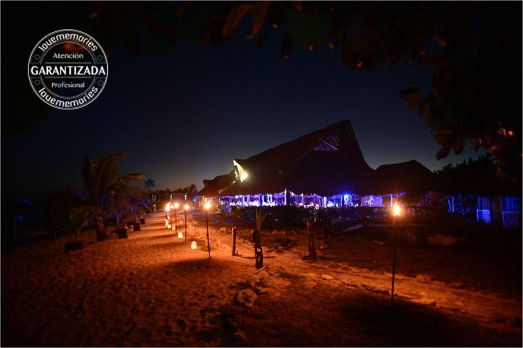 A line of torches and solve decorate light on events on the beach www.lovememories.com.mx