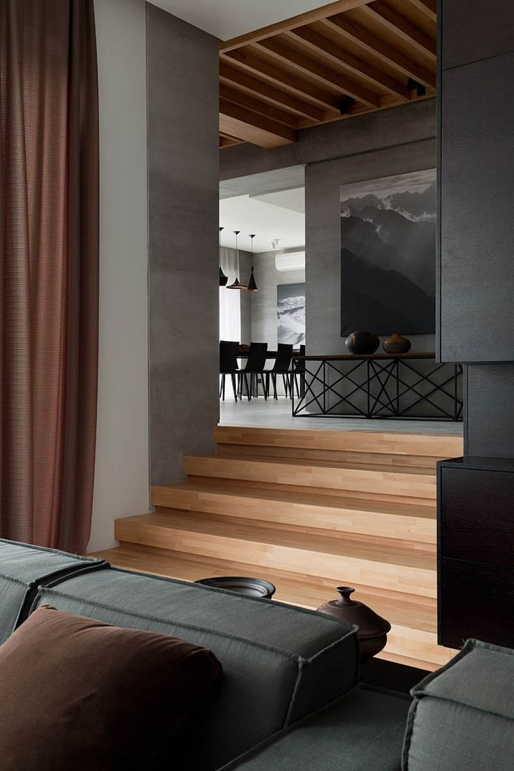 Multilayered living room layout. Dark and moody walls help set the atmosphere.