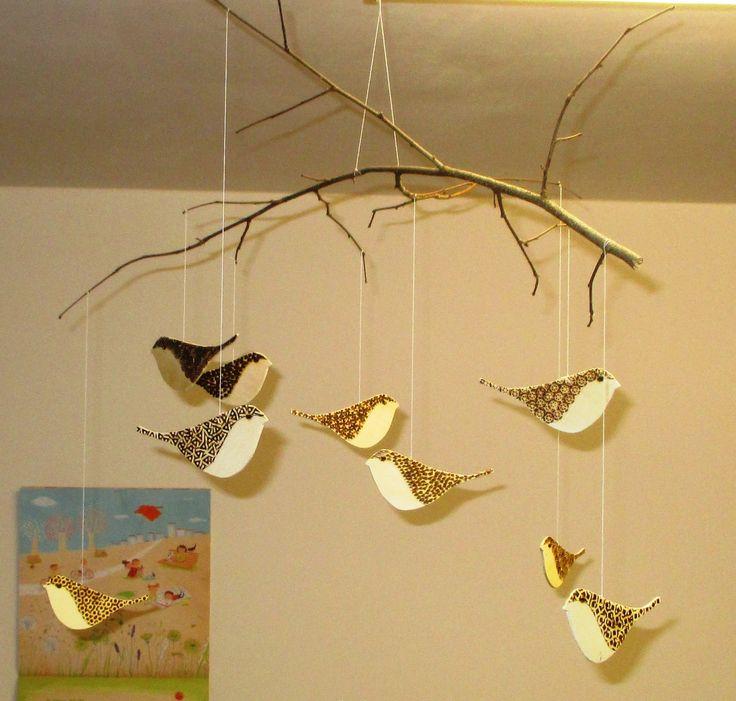 """Mobile con uccellini di compensato decorati con pirografo da """"persone con handicaps"""" e montati su ramo vero."""