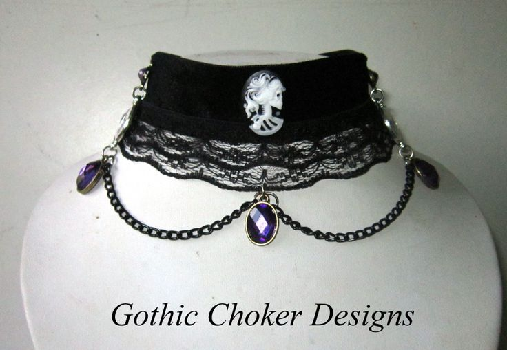 Gorgeous black velvet and ruffled lace choker with resin skull cameo in the centre, with two printed skull cameos on the sides and decorated with black chains and purple stones.  Please note that the stones are a brighter purple than has been captured on the photograph.   R180 Purchase here: https://hellopretty.co.za/gothic-choker-designs/gorgeous-choker-with-skull-cameos-and-purple-stones