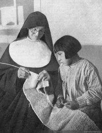 Monja enseñando a tejer a una niña selknam