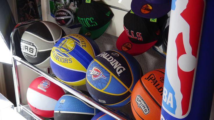 #Pelotasbaloncesto de goma para fans de la #nbafan en un carro de balones. En el fondo gorras de equipos de baloncesto NBA y Euroliga. www.basketspirit.com