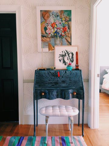 Love the mix here: light, tone-on-tone wallpaper pattern, DIY cerused desk in indigo, striped rug, padded seat, artwork and brass lamp.  It all works so well! --LYC