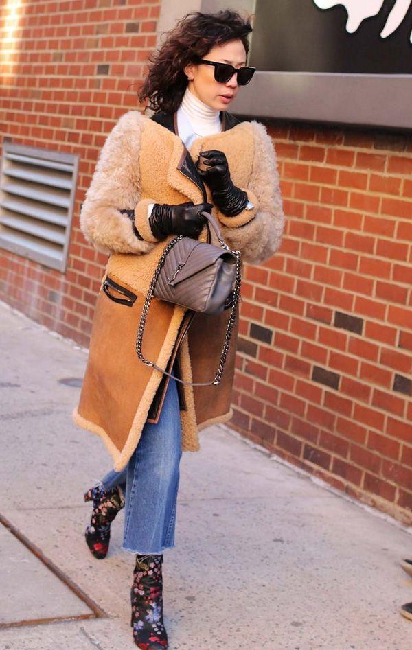 Look de inverno com calça jeans cropped + sobretudo marrom com detalhes de pêlo.