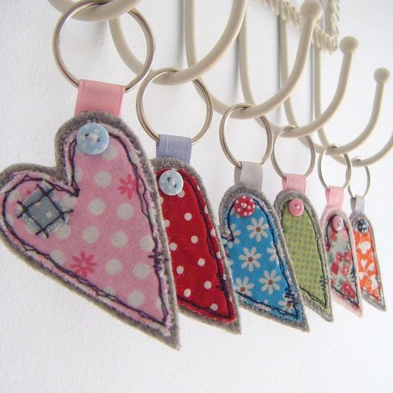 This fabric heart keyring has been handmade using pretty cottons, appliqued onto a hardwearing quality wool fabric.  Made using a freehand machine embroidery technique, and then finished with a cute mini button.  Makes a beautiful gift for teachers, friends or family.  Measures 4cm x 6cm  Available in Blue, Pink, Green, Floral and Red  Comes with metal keyring  5 pounds: