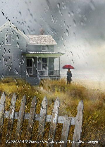 Trevillion Images - man-with-umbrella-near-seaside-cottage