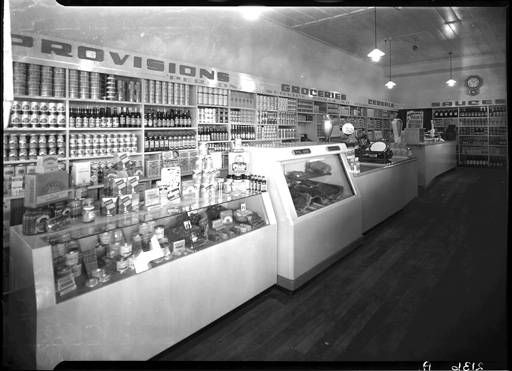 Old fashioned grocery store interior in Kingsview Road, Mt Eden. Rows of bottles and tins on shelves - gleaming counters. Four Square advertisement. PH-NEG-2136A