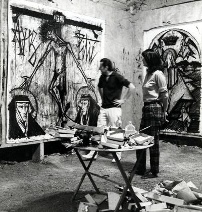 """B. Руководство - Бернард """"шведский Стол"""" в своей мастерской, позируя перед его картинами, 1961."""