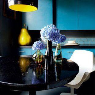 Cuisine bleu pétrole avec placards, et poire en papier mâché, ainsi qu\'une table ronde noire laquée