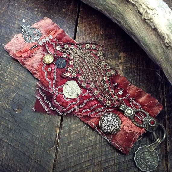 A tattered red, dusky pink and gold embroidered textile cuff, primitively hand stitched and pieced together using recycled fabric and found elements: