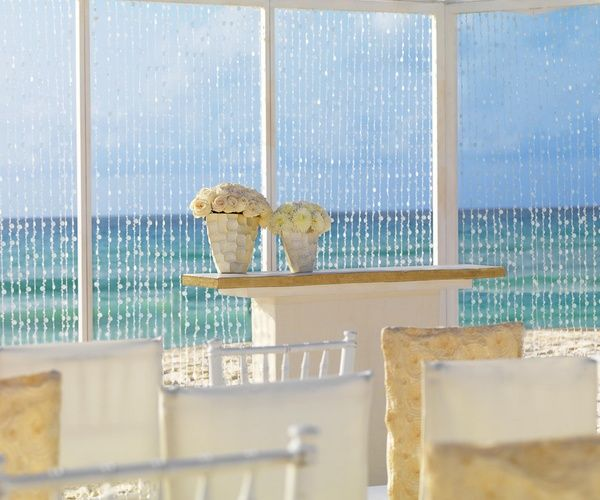 Sea glass beaded curtain and white florals at altar canopy for beach wedding ceremony | Pearl Shimmer Collection at Palace Resorts #destinationwedding