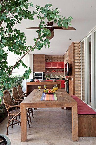deixar o espaço com cara de área externa, com escolha de cimento queimado e madeira. Pintados de vermelho, os armários guardam utensílios para churrasco