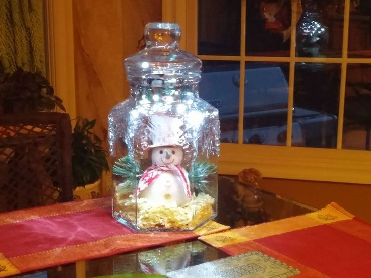 Glass decanter jug decorated for holidays. Use battery operated lights with timer. No plug in and you don't have to remember to turn them on and off. Great centerpiece.