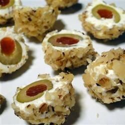 Stuffed Spanish olives are wrapped in a spiced cream cheese mixture and rolled in chopped nuts for an easy appetizer.