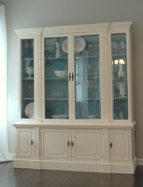 white cabinet with blue background, makes dishes pop.... with different shade blue/gray walls.  Newlywed Nesters