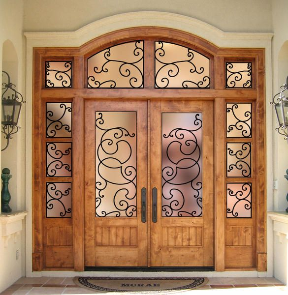 Custom Country French Exterior Wood Entry designed with one lite glass in the doors, flat V-Grove lower panels, matching divided lite sidelites and a 4 piece transom. The glass is clear beveled insulated glass and Wrought Iron Grills