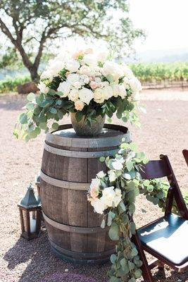Ceremony seating with fresh greenery and white flowers wine barrel lantern bouquet of flowers blush