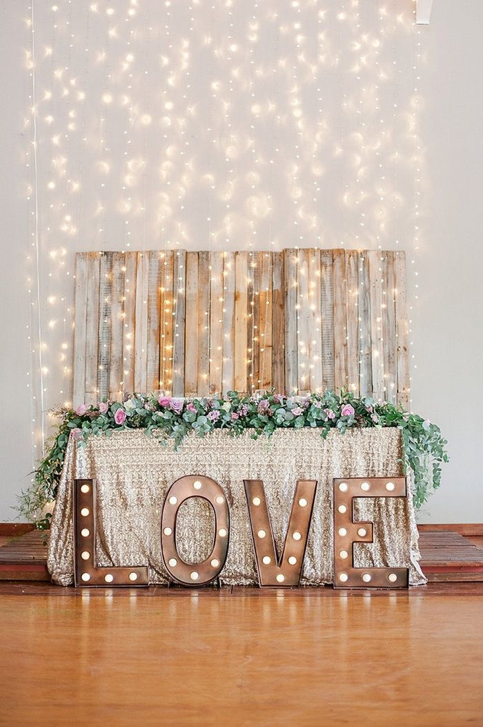 This sweetheart table is exactly what our hearts desire. Marquee letters, pallet wood, sparkles, string lights, and greenery - sigh.