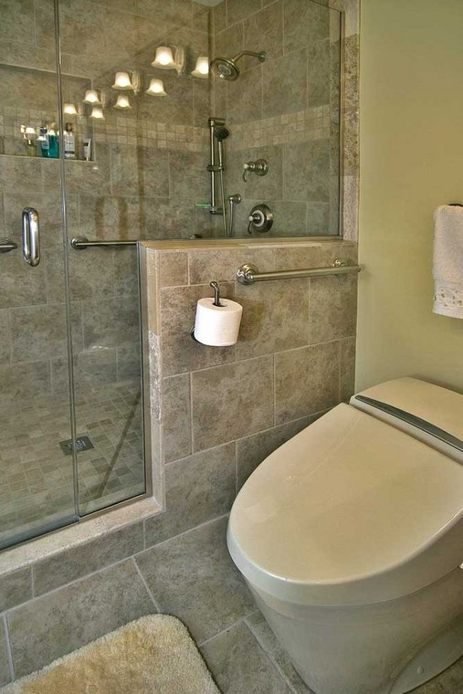 The grab bar above the toilet matches those inside the stone tile shower. The toilet is comfort-height.