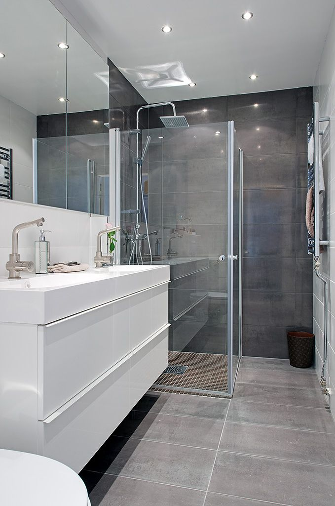 White modern bathroom- grey tiles, floating glass shower, ikea vanity, small recessed lights