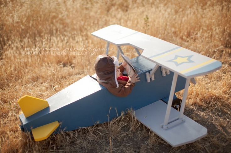 Boy riding in wooden toy airplane. Airplane themed first birthday photos.