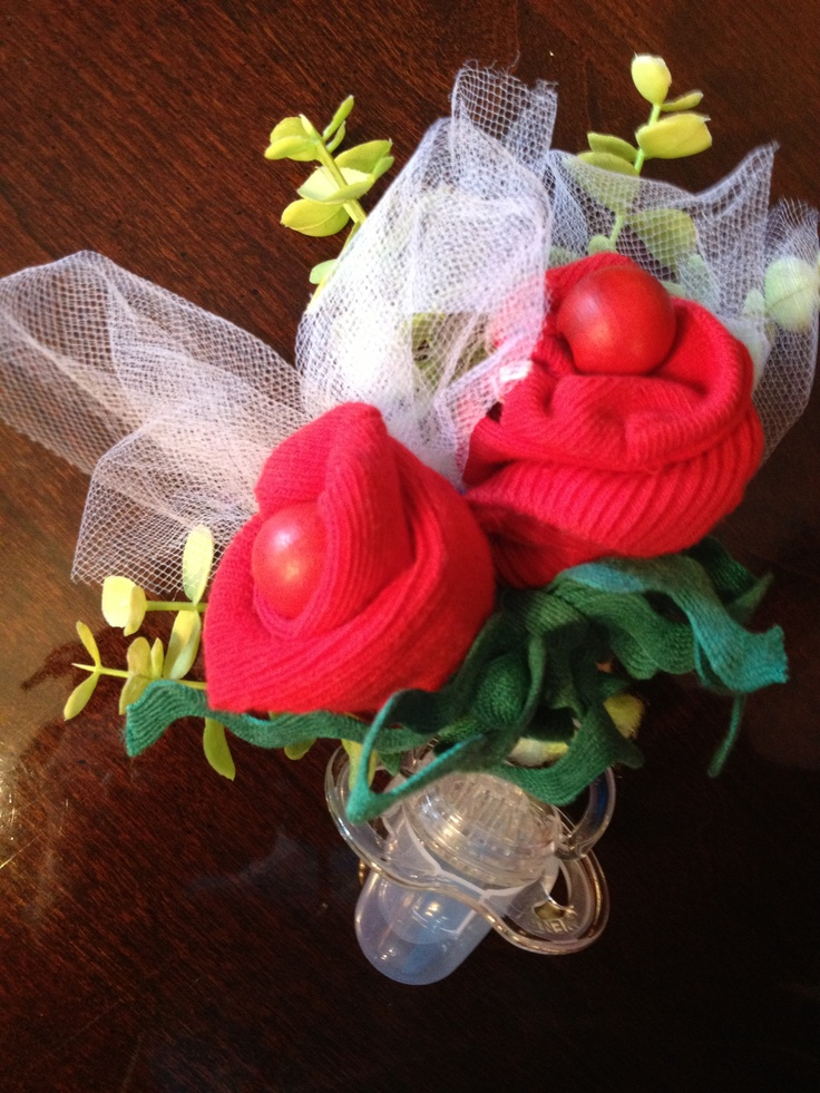 A corsage of socks and a bead with a pacifier and trim.