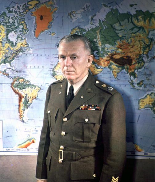 Portrait of General George C. Marshall (1880 - 1959), General of the Army, standing in front of a world map, Washington, DC, 1945. (Photo by PhotoQuest/Getty Images)