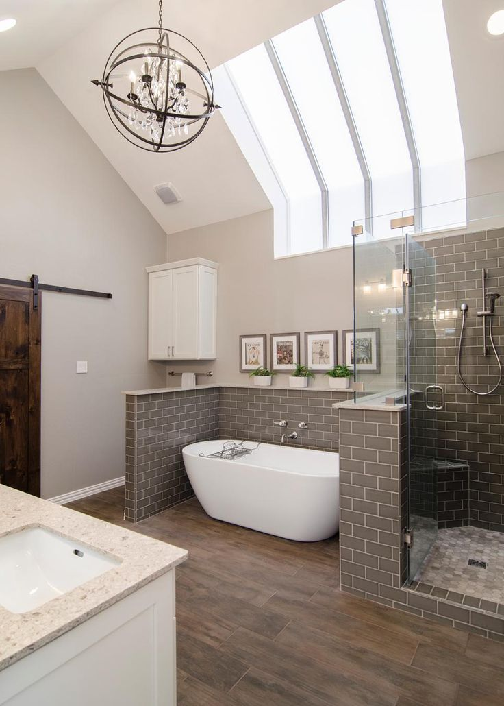 This beautiful spa bathroom combines unique details—like the orb-shaped chandelier and vertical skylight stripes—with classic elements for a refreshing, relaxing space. Gray tile smartly wraps around the shower and soaking tub; wide-plank wood floors and a sliding barn door bring a softening earthy touch.