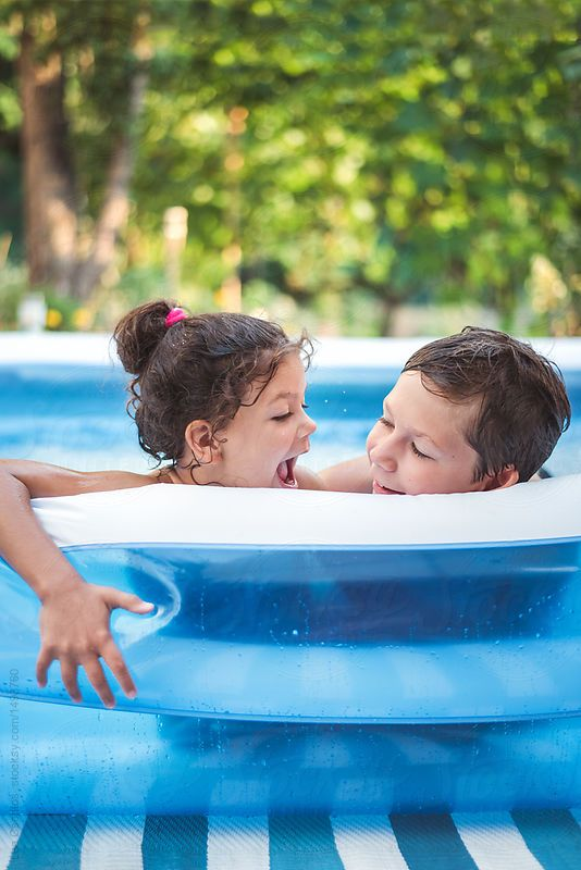 Kids having fun in an inflatable pool on a hot summer day by Lea Csontos for Stocksy United