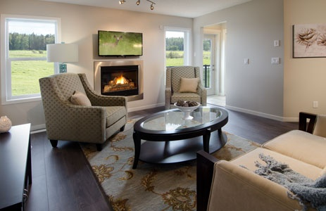 Luna - Great Room complete with modern fireplace, olive printed cloth chairs and cream sofa with a blue throw