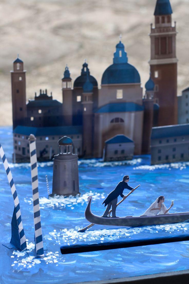 Urne boîte à cadeaux pour soirée de mariage sur le thème de Venise. Le décor dessiné est découpé et assemblé en plusieurs plans sur le couvercle de la boîte. La mer est peinte à l'acrylique. A l'arrière du décor, une guirlande de lampes leds éclaire les fenêtres ouvertes.