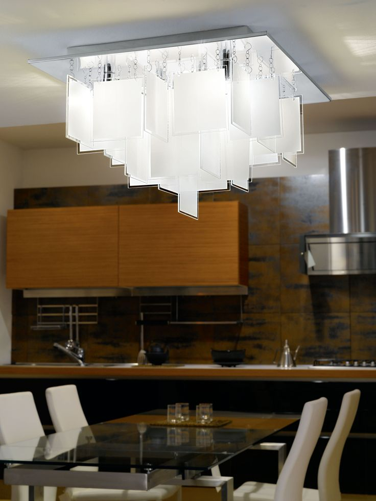 CONDRADA 1 es el nombre de este modelo de lámpara de techo con base cuadrada de metal cromado. Los vidrios dispuestos perpendicularmente entre sí, dan forma a esta luminaria con elegancia. Viene en 3 medidas: 37, 47 y 77 cms por lado y de 5, 8 y 16 luces respectivamente. Si te gusta el orden, la geometría y el calce perfecto seguro alucinarás con este diseño.