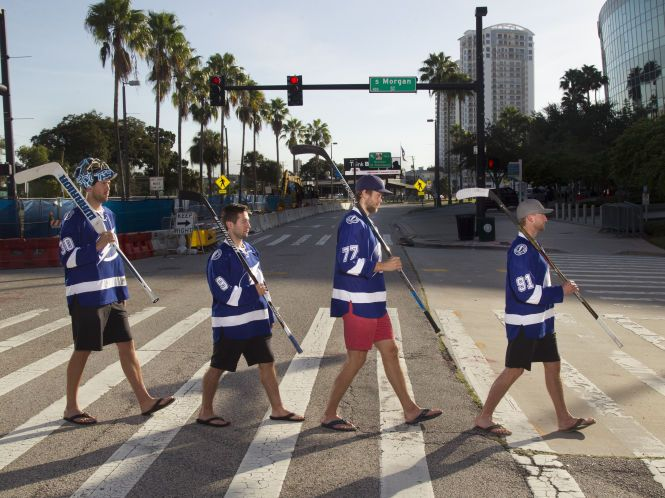 Special section cover for the opening of the 2016-2017 Tampa Bay Lightning season. The Band is Back Together! Break out the vinyl with this Abbey Road Beatles album cover recreation. From left is Tampa Bay Lightning goalie Ben Bishop (30), center Tyler Johnson (9), defenseman Victor Hedman (77) and center Steven Stamkos (91).  Instead of crossing Abbey Road in London, this fab four is crossing Channelside Drive with the Amalie Arena up ahead on right.