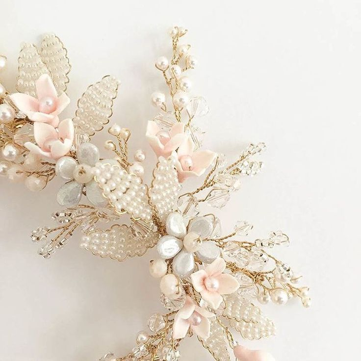 Soft pink handmade flowers set amongst ivory, silver and gold details