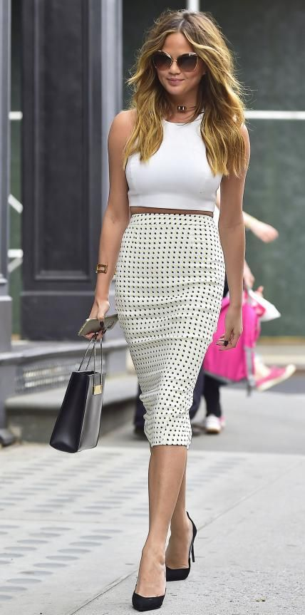 Chrissy Teigen in a white crop top and A.L.C. pencil skirt.