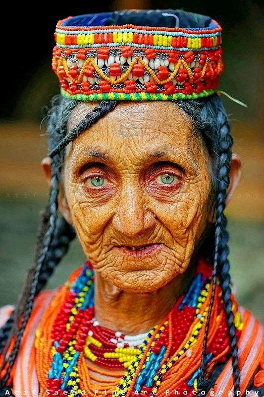An old Kalash woman wearing colorful beaded jewelry that ...