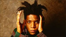 Jean-Michel Basquiat looks into the camera from a seated position with his hands held up framing his face.