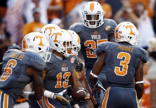 Tennessee's Devaun Swafford (13) is congratulated by Vincent Dallas (6), Byron Moore (3), and Justin Coleman (27) after scoring a touchdown during the second half ofan NCAA college football game against Georgia on Saturday, Oct. 5, 2013, in Knoxville, Tenn. Georgia won 34-31. (AP Photo/Wade Payne)